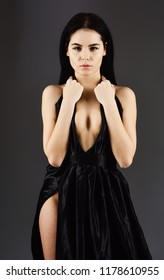 Lady, sexy girl in dress. Attractive girl wears expensive fashionable evening dress with erotic slit. Sexy decollete concept. Woman in elegant black evening dress with decollete, dark background.
