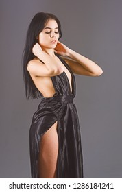 Lady, sexy girl in dress. Attractive pensive girl wears fashionable dress with erotic slit on hip. Fashion and vogue concept. Woman in elegant black long evening dress with nude back, dark background.