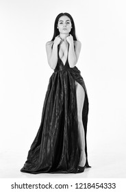 Lady, sexy girl in dress. Woman in elegant black long evening dress with decollete, white background. Fashion dress concept. Attractive girl wears expensive fashionable evening dress with erotic slit.