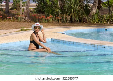 Lady sexy with swimsuit sit on pool, in Chumphon province Thailand.
