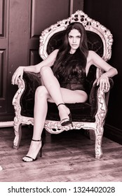LAdy sittin in a big chair