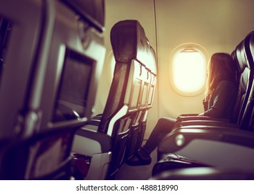 Lady is sitting in airplane looking out at shiny sun through window, vintage style photo
