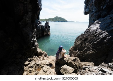 lady sitting in the cave sea looking view at koh Sichang, Thailand
