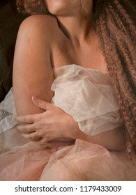 lady sitting in a dark bedroom with tulle petticoat