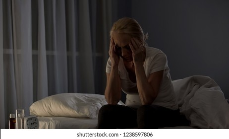 Lady sitting on bed, unable to fall asleep due to severe migraine and bad pain