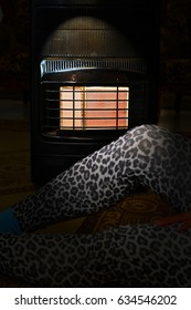 A lady sitting on a carpet near a gas heater in the dark with window light in a cold night and power failure in the house