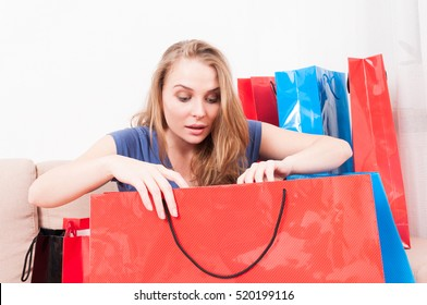 Lady sitting on couch looking in her shopping bags and acting very curious