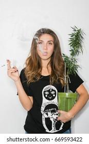 Lady smokes marijuana and marijuana bush, cannabis