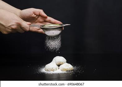 "A Lady sprinkling sugar on Kahk feast ""Kahk El Eid"" - Translation : Cookies of El Fitr Feast"