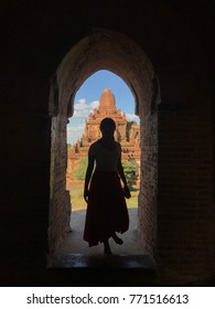 Lady stand inside pagoda door, silhouette shot with pagoda and sky in background.