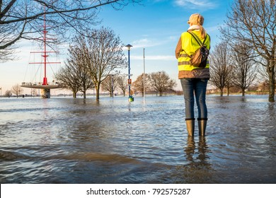 Lady standing in flooded street in wellys