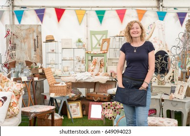Lady standing in front of craft stall with bunting, vintage wares, crafts and retro ornaments