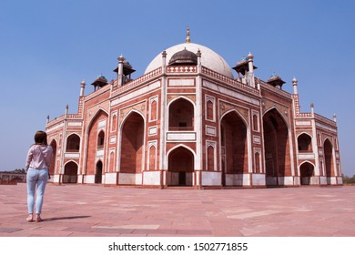 A lady standing next to the Humayun's tomb, one of the remnants of the mughal dynasty in India. The resting place of the mughal ruler Humayun