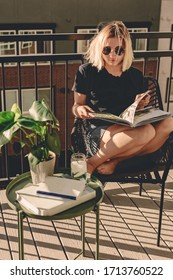 Lady in summer outfit and sunglasses reads book on the balcony. View from the balcony. Sunny day. Relaxing time. Cucumber iced water. Blonde girl stays home. Large balcony. Patio. Warm sunny day.