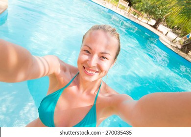 Lady taking a selfie at resorts poolside on summer vacations. Holidays and vacations.