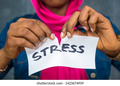a lady tearing up a paper with stress written on it