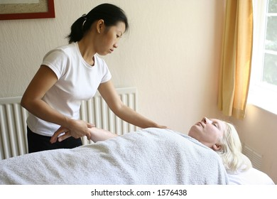 A lady therapist giving a holistic massage to her client
