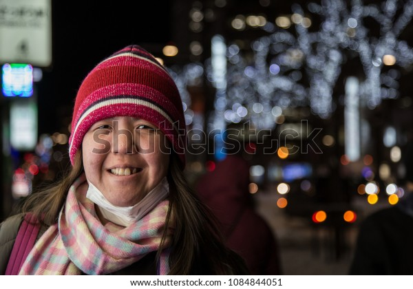 Lady travel in Sapporo city with bokeh light as background, Hokkaido, Japan during winter season