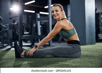 Lady turning her head with a smile while having a seat on the floor and rubbing the ankles