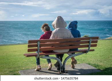 Lady and two children sitting on a park bench at beach - cold and windy.