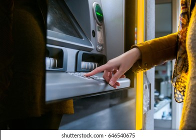 Lady using ATM machine to withdraw her money. Close-up of hand entering PIN/pass code on ATM/bank machine keypad. Finger about to press a pin code on a pad. Security code on Automated Teller Machine.