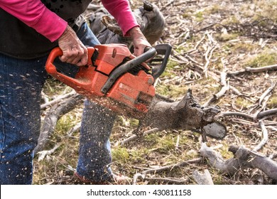 Lady using chainsaw to cut a log for firewood creating saw dust.