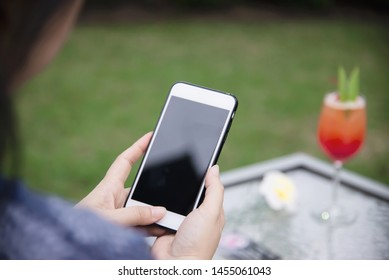 Lady using mobile phone relax in green garden with soft drink background - people and technology lifestyle concept
