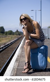 Lady waiting for a train sitting on her luggage