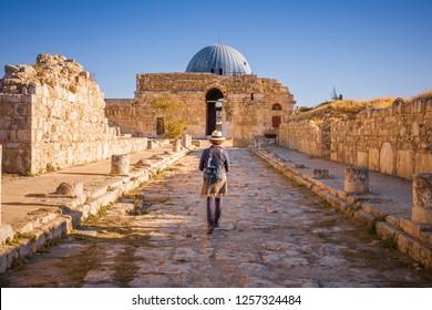 Lady caminando por la calle Colonnated hacia el Monumental Gateway en el Palacio Umayyad, Amman Citadel, Ammán, Jordania