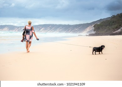 A lady walking her Dachshund dog along a sandy beach with rain clouds in the sky above the sand dunes