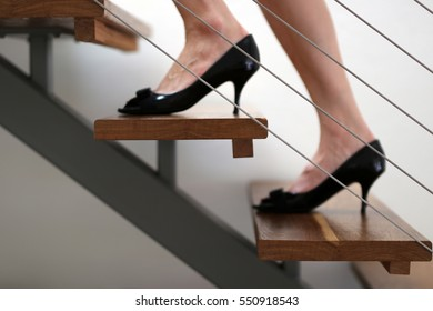 Lady walking up the metal and timber staircase with business black patent leather pumps shoes
