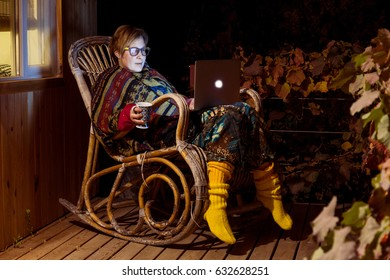 Lady in warm traditional clothing sitting on rocking Chair at outdoor Terrace of wooden Hut located in suburban Forest Freelance work Concept
