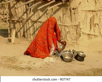 a lady washing utensils in a village in india