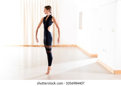 Lady wearing black ballet wear in dance studio, heels raised and with arms in starting position