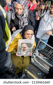 A lady in a wheelchair is pushed through a crowd of people whilst holding a sign with the Ayatollah's face on it during the Quds Day rally, London, 10/06/18.