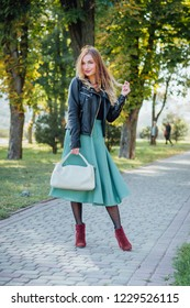 Lady with white bag and wearing a leather jacket, top, turquoise sun skirt and suede boots walking in the city street. Fashion conception. Sunny ligth behind her back.
