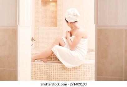 Lady in white bathrobe preparing for a hot bath.