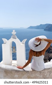 Lady in white dress and white hat sitting next to a church bell tower and embracing the view of the caldera