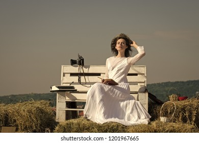 Lady in white dress and wreath on sunny day. Education and knowledge. Summer vacation concept. Woman reading book on blue sky. Girl with vintage typewriter and camera on bench.