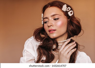 Lady with white hairpins in curly hair plays with her pearl necklace and gently looks down