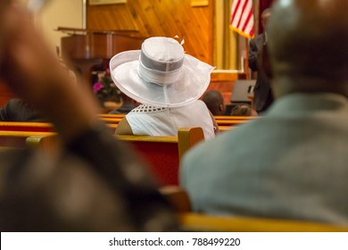 lady with white hat in church