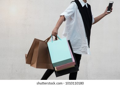 The lady in white shirt is carry colorful shopping bags with right hand and hold mobile phone with left hand,shopaholic lady.