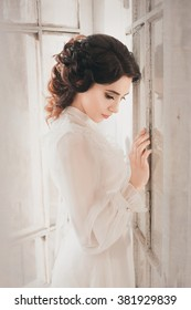 Lady in white vintage dress standing in a large spacious room near the window , fantastic shot, fairytale princess , trendy toning , creative computer colors