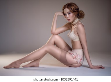 Lady in white vintage retro lingerie posing at camera