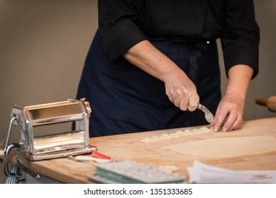 Lady who cuts Italian agnolotti dozen with a pasta cutting wheel on a wooden cutting board