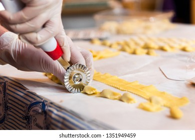 Lady who cuts Italian agnolotti with a pasta cutting wheel on a white tablecloth