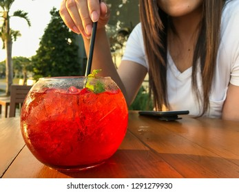 The lady will drink strawberry soda by her hand hold up straw and feel fresh
