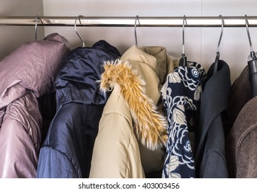 Lady winter clothes hang in wardrobe