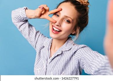 Lady without make-up in sleepwear smiles and shows sign of peace. Blue-eyed woman makes selfie on isolated background