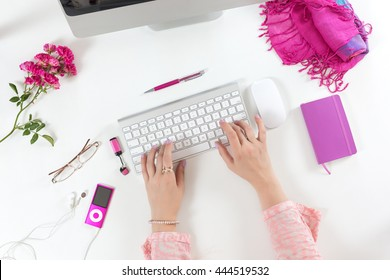 Lady working on Computer at White Desk with red and pink Business and Lifestyle Items Top View